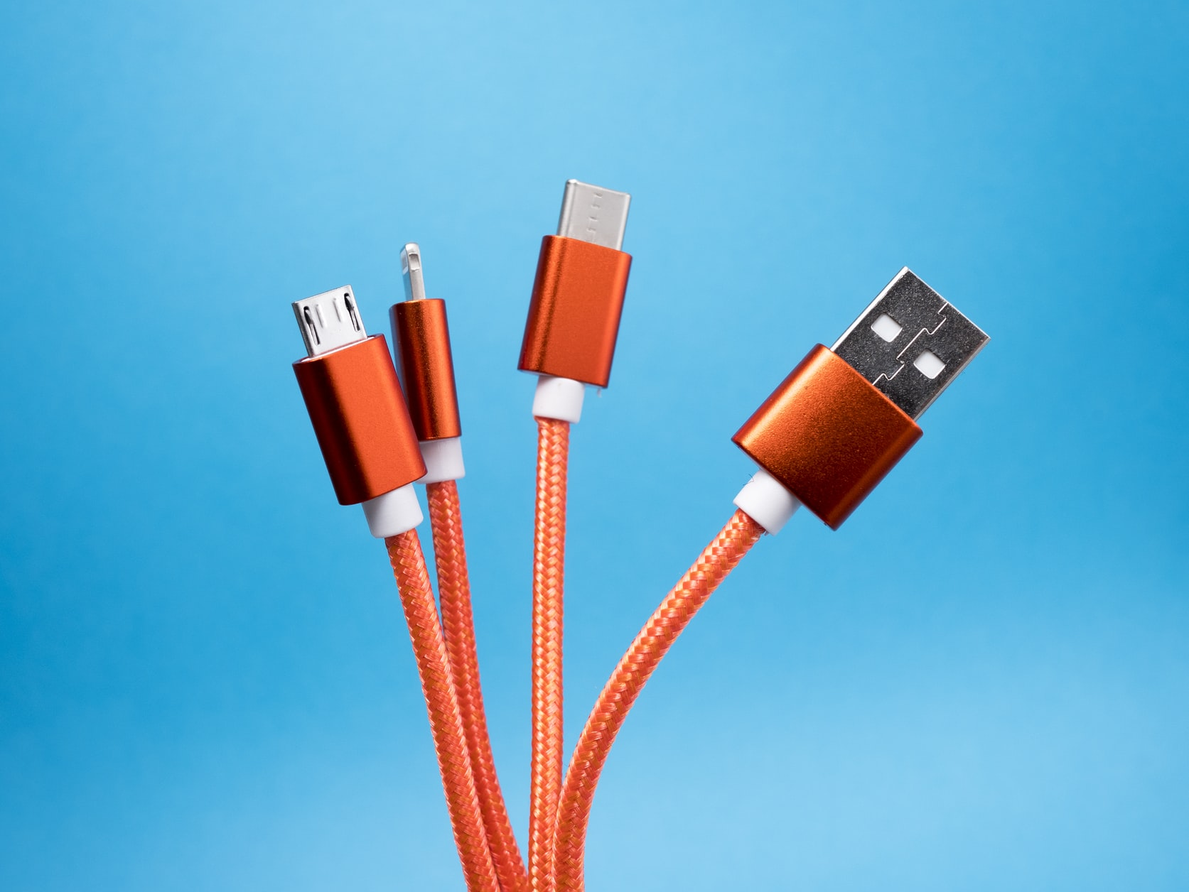 A group of orange charging cables against a blue background